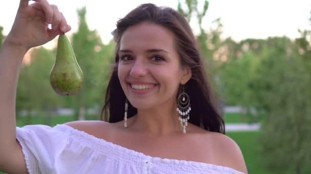Mladá žena s hruškovým ovocem. Krásná brunetka žena jíst šťavnaté zralé hrušky