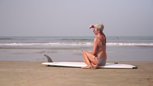 Atraktivní starší žena surfování a venkovní aktivity na pláži