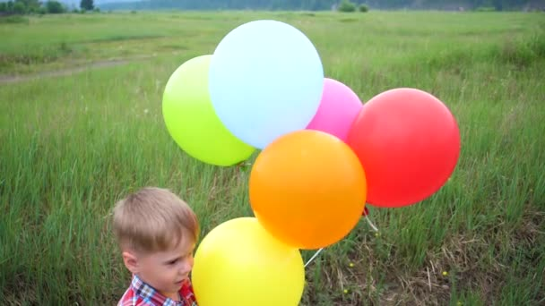Happy little baby, fun playing with balloons. Outdoor recreation. Celebration and fun.