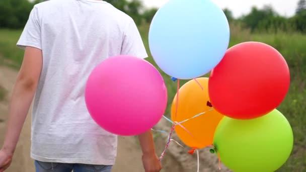 Šťastné děti běžet na lesní cestě s balonky. Oslava narozenin v parku. Smích a radost dětí
