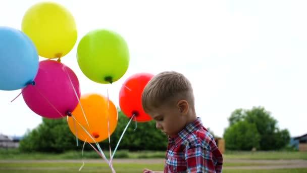 Šťastný kluk si hraje s balón v parku. Turistické a outdoorové aktivity