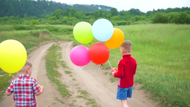Happy children run on a forest road with balloons. Birthday celebration in the Park. Laughter and joy of children