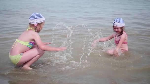 zwei Mädchen spritzt sich Wasser auf den Strand. Zwillinge Gießen Sie Wasser auf einem heißen Sommertag, lachen und gute Laune der Kinder