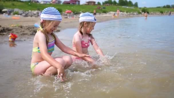 Zwei kleine Mädchen gießt Wasser am Strand. Kinder spielen, lachen, Spritzer zu erstellen. Sommerurlaub am Meer