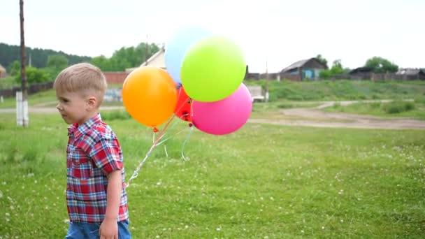 fröhlicher Junge spielt im Park mit Luftballons. Wandern und Aktivitäten im Freien