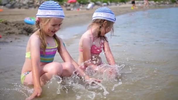 Zwei kleine Mädchen spielen am Meer. Kinder, goss Wasser, erstellen Spray. Heißer Sommertag, gute Laune
