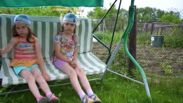 Two girls sisters swing on a swing. Entertainment and outdoor recreation. Summer day.