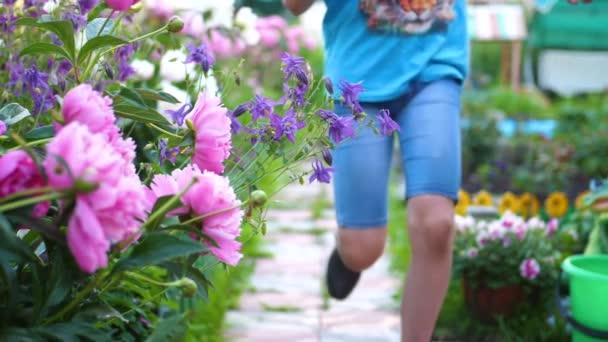 Los niños corren a lo largo de la ruta a lo largo de las flores. Dos niños  juegan en el jardín de flores. Infancia feliz