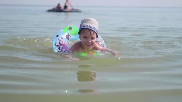 Dítě plave na nafukovací kruh v moři. Šťastné dětství. Pozitivní emoce