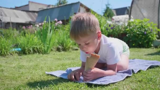 A little boy lying on the lawn and happy to eat ice cream. Hot summer day, cold sweet dessert