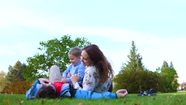 Happy family lying on the lawn. Mother and father playing with his son, the child smiles. Against the background of the sun and sky, happy faces of parents and child.