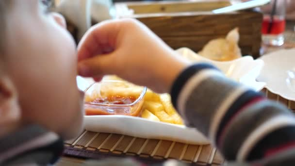A child in a fast food cafe eating fried potatoes in a plate. Hand close up. Slices of potatoes, fried in oil