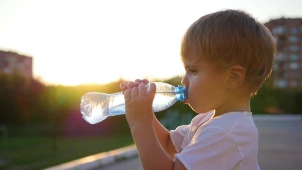 miminko pije vodu z láhve venku. Čas západu slunce