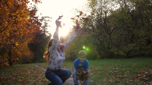 Mother and child in the autumn Park throws yellow leaves. Laughing and smiling happy family