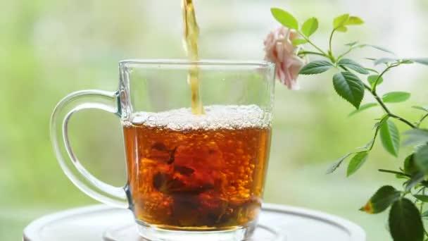 Nalít čaj s listy rybízu, citrónový balzám, máta, malina ve skleněném šálku.Čaj party venku