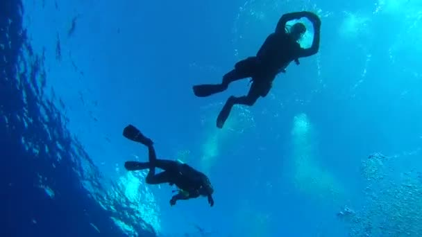 INDIAN OCEAN, MALDIVES, ASIA - MARCH 2018: A young pair of scuba divers hanging in blue water at safety stop - Indian Ocean, Fuvahmulah island, Maldives, Asia