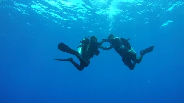 INDIAN OCEAN, MALDIVES, ASIA - MARCH 2018: Young couple of scuba divers dances underwater in blue water at safety stop - Indian Ocean, Fuvahmulah island, Maldives, Asia