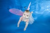 Fotografie Schöne Babymädchen in Fee Kostüm Schwimmen unter Wasser auf blauem Wasser Hintergrund. Gesund Leben mit Familie und Kindern Wasser Sportaktivität. Entwicklung des Kindes, Prävention von Krankheiten
