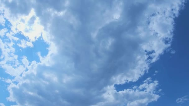 Time lapse, Beautiful skyscape with large gray clouds and sun rays breaking through cloud mass. Heavenly clouds with bright sun rays on blue sky. Sun rays and gray clouds in blue sky.