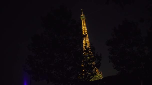 Eiffel Tower glows with bright lights the spotlight beam at the top