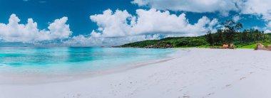 Idyllic panorama sea cloudscape of Grand Anse beach in La Digue island, Seychelles. Pristine white sand and clear azure water. Exotic landscape