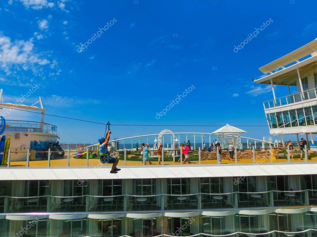 Cape Canaveral, USA - April 29, 2018: The passenger at zip line at cruise liner or ship Oasis of the Seas by Royal Caribbean docked in Cape Canaveral, USA on April 29, 2018. The air attraction is