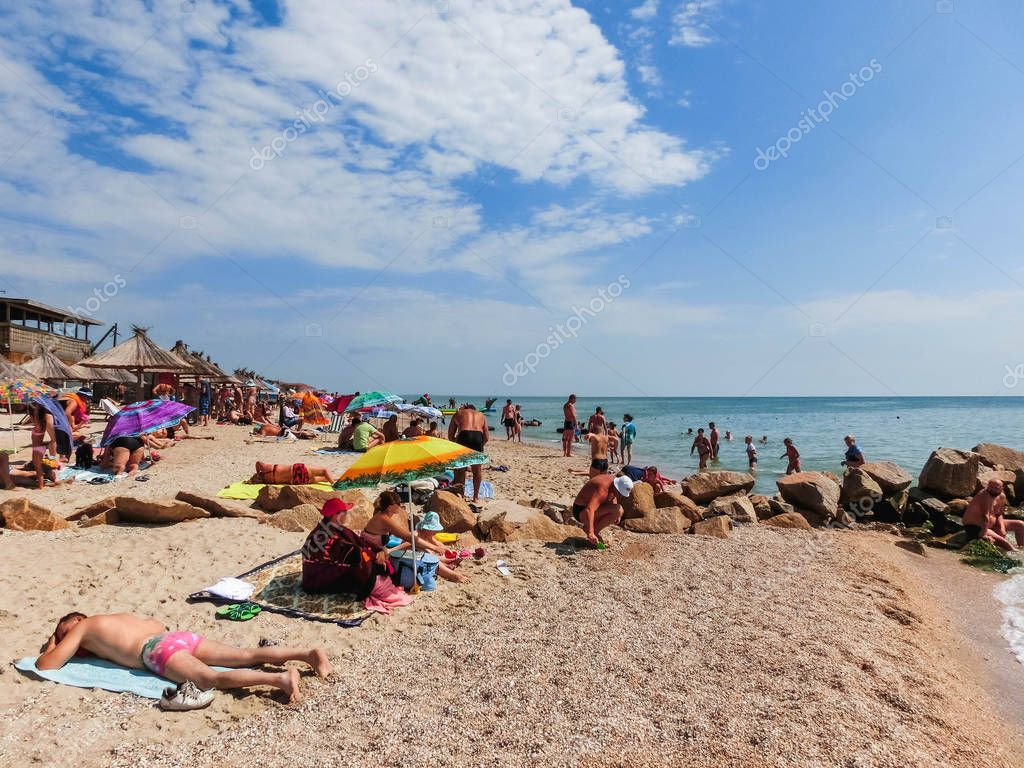 Berdyansk, Ukraine June 30, 2018: beach resort seasonon the coast of the Azov Sea. People are sunbathing on the beach.