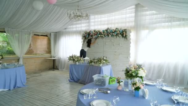 Decorating wedding banquet hall interior. Beautiful florist creating spring colorful flowers bouquet arrangement. Process of preparing floral composition for celebrating party.