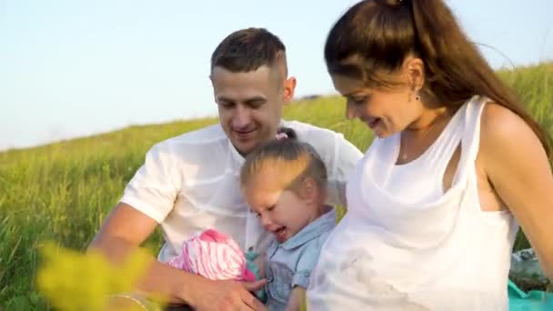Closeup pregnant couple with toddler daughter have leisure time outdoors in grass field on blanket