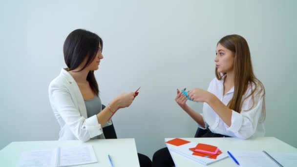 two female high school students sitting in classroom and having conversation tutorial