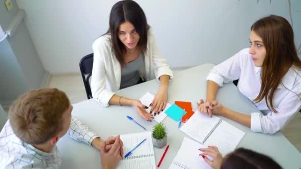 középiskolás diák csoport megvitatása és megoldása projekt-hozzárendeléskor asztalnál együtt