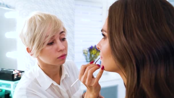 closeup female makeup artist applying lip gloss on young woman face with brush at beauty salon