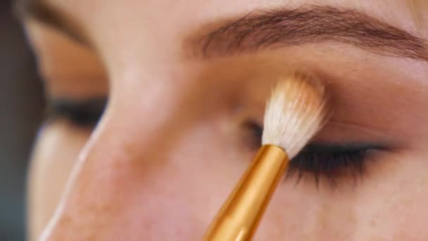 closeup face of red hair young female getting professional eye makeup with brush