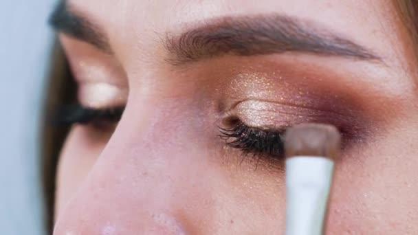 make-upu štětec použití eyeshadows na krásná mladá žena víčka closeup