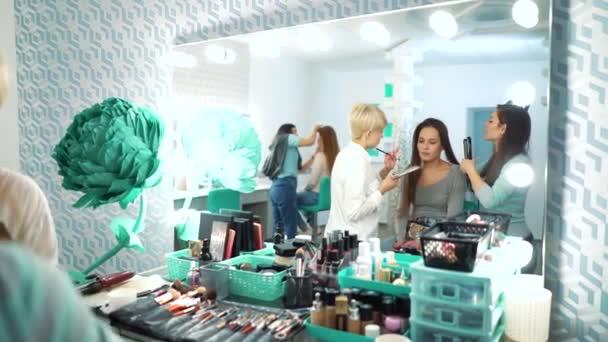 Odraz v zrcadle žen v salonu kosmetika, make-up a účes
