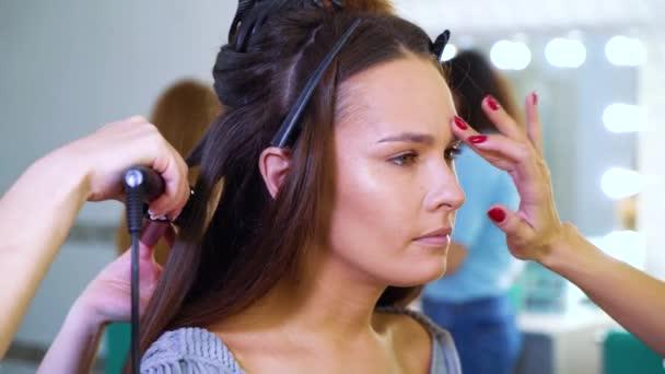 Closeup salon krásy dívek dělá účes a make-up pro atraktivní mladá žena