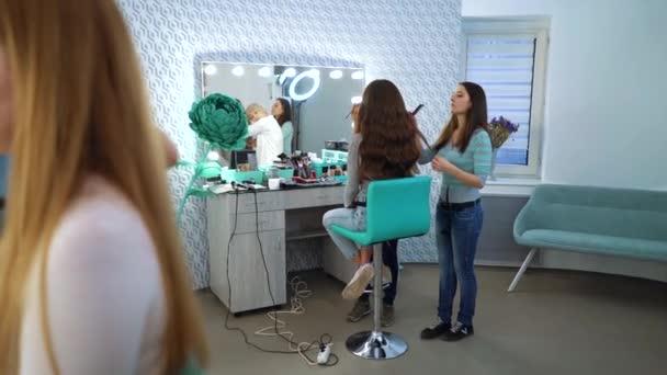 posouvání záběr salon krásy dívek dělat profesionální make-up a účes pro mladé ženy