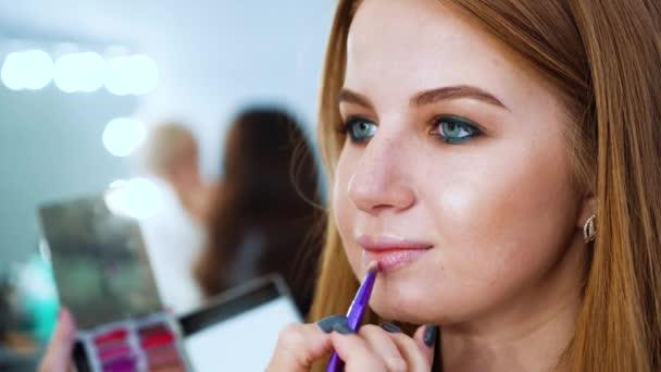 Detailní podobu atraktivní mladá žena získání profesionální make-up v salonu krásy