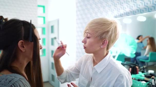 Maskérka použití tvář nadace štětcem na ženách tvář ve světle kosmetika salon.