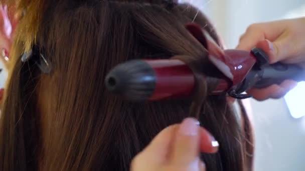 Closeup ženské ruce pomocí kulma na vlasy pro dlouhé tmavé vlasy