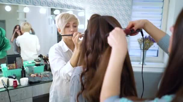 zrcadlový odraz vizážista a kadeřník dělá make-up a účes pro roztomilá mladá žena