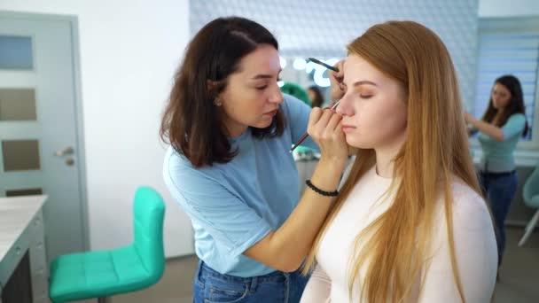 posouvání záběr vizážistů a kadeřník dělá make-up a účes pro ZÁKAZNICÍM