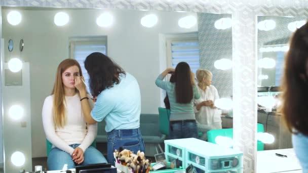 zrcadlový odraz ženské maskérka použití kosmetiky na mladou ženu v beauty salonu