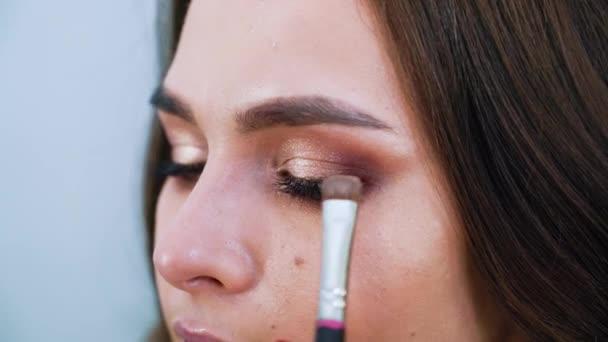 Detailní ženský ruce vyrovnávací eyeshadows na roztomilý mladých ženách víčka pomocí speciální štětce