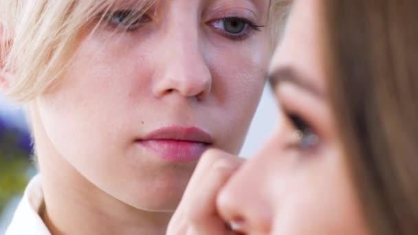 maskérka použití kosmetiky na detailní obličej mladé ženy