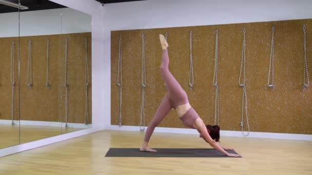 Fiatal nő csinál jóga asana a jóga stúdió, ban lassú mozgás