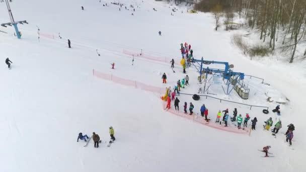 letecké skupiny lyžařů a snowboardistů čekání na vlek, lítají po zasněženém svahu