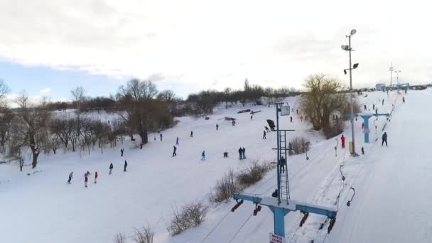letecký lyžařů a snowboardistů sjíždění zasněženého svahu a jízdě s vlekem