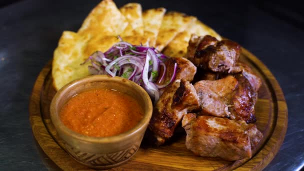 Detailní pohled na dřevěném prkénku s grilovaným masem, tortilly, omáčkou, nakrájenou cibuli na něm. zdravé, chutné jídlo