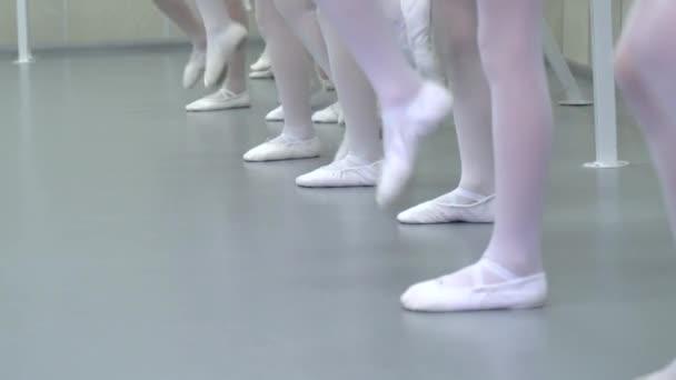 Closeup nohy malé baletky skupiny v bílých botách v řadě cvičení ve studiu klasického baletu